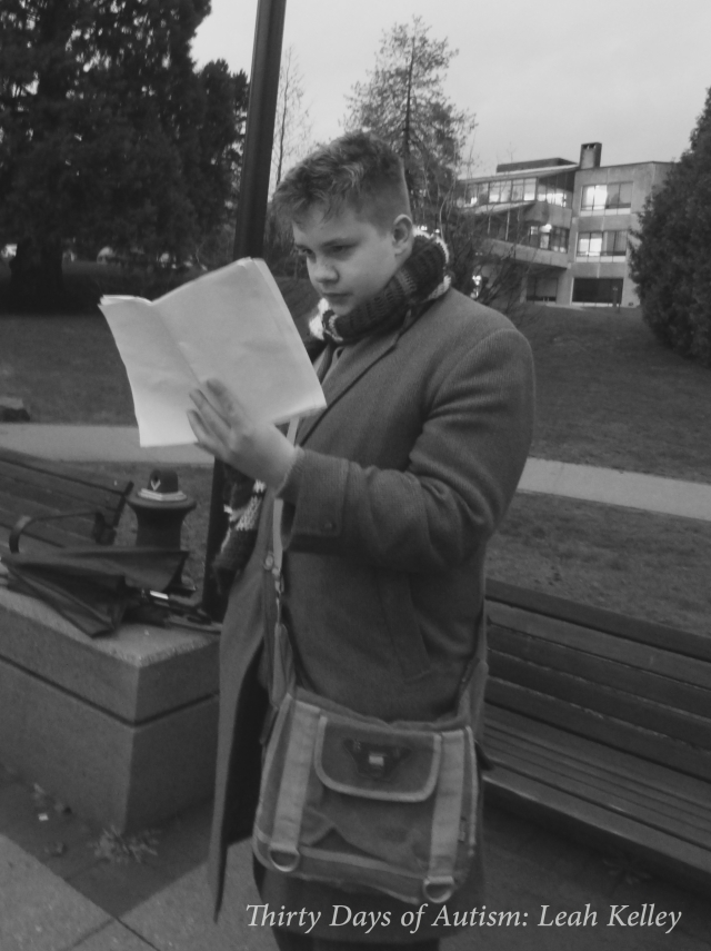 Black and white photo of H (a white male teen with spikey hair, a retro woolen tweed trench coat, a Doctor Who scarf and a messager bag) looking at the 10 page list of disabled people who killed by their families or caregivers.