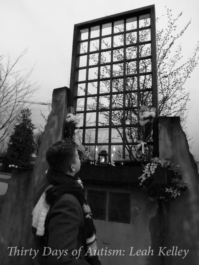 Black and White photo of H looking up at and art installation represent cement walls with the barred windows of Woodlands Institution. This is has been recreated so that it is the same height that the windows would have been for the residents. There are candles and flowers arranged on the window's ledge, and a tree can be seen through the bars.