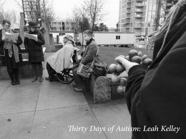 Black and white photo of Emma and Alanna reading the names of disabled people who have been murdered. NOrm and Harrison are listening. The arm of a mourner is visible in the foreground, holding a stim toy.