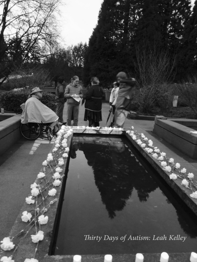 Black and white photo of the reflecting pool surrounded by a lattice work of white carnations and people who participated in the Day of Mourning. They are gathered around and talking after the vigil.