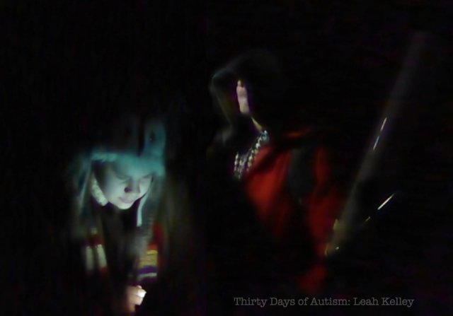 """Cosplay Stargazers"" Image: H looking downwards, dressed in vintage wool trenchcoat, Dr Who scarf and owl hat and K standing behind, mostly hidden by darkness and a hooded cape over a red/orange jacket. K appears to be holding a wooden staff. The background is night black with lighting from below."