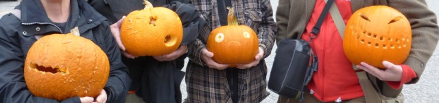 The arms and bodies of 4 warmly clothed people holding carved pumpkins.