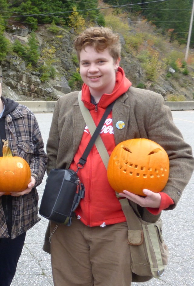 Image: H holding his pumpkin in a parkinglot.