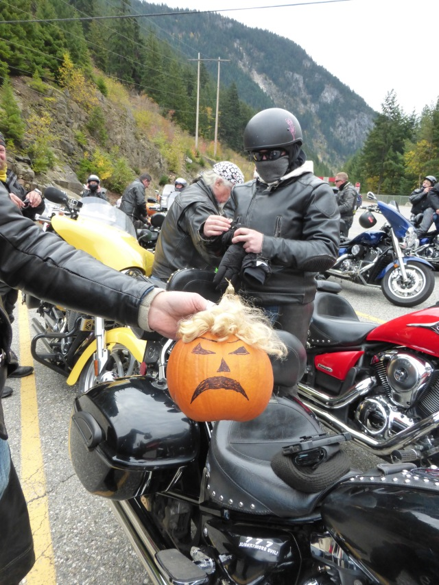 """A motorcyclist holing a frowning pumpkin with a shock of unruly yellowish hair. He told me it was """"Donald Trumpkin"""""""