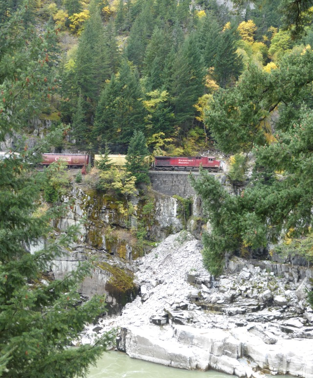 Image: A view across the canyon where a trainis visible on the tracks. The red engine says